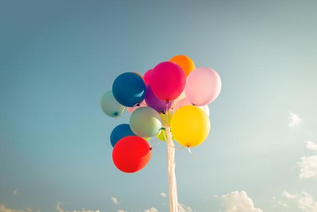 Ballons de fête colorés sur ciel bleu avec un effet de filtre instagram vintage rétro