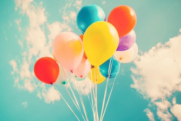 Ballons de fête colorés sur ciel bleu avec un effet de filtre rétro vintage instagram.