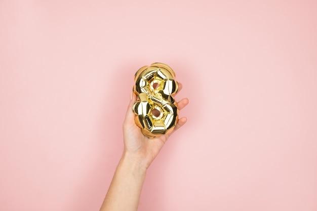 Ballons en feuille d'or chiffre 8 dans la main féminine sur une surface rose. joyeuse journée de la femme