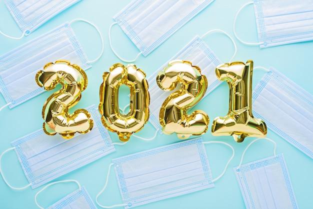 Ballons en feuille d'or numéros 2021 avec masque médical sur bleu
