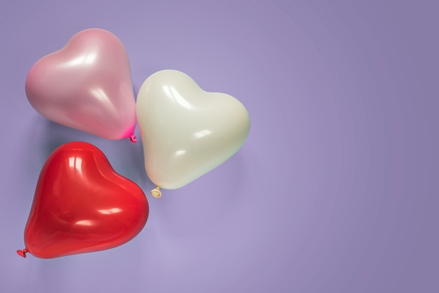 Ballons en forme de coeur sur surface violette