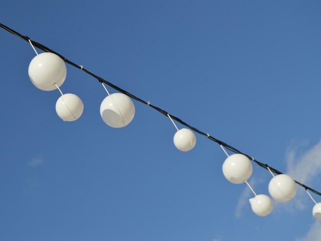 Des ballons de guirlandes blanches oscillent dans le vent contre le ciel bleu et les nuages, paysage paisible