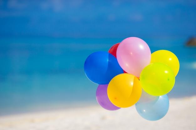 Ballons multicolores sur une plage tropicale blanche