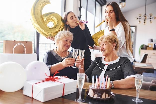 Ballons avec le numéro 60. senior woman with family and friends célébrant un anniversaire à l'intérieur.