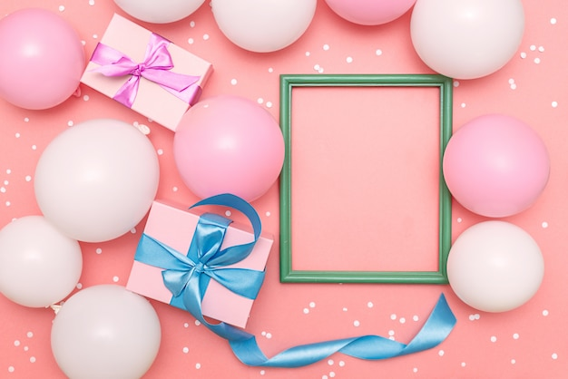 Ballons pastels et confettis blancs sur fond rose