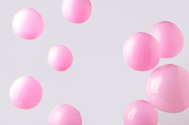 Ballons pastels roses sur fond gris. minimalisme. vue de dessus