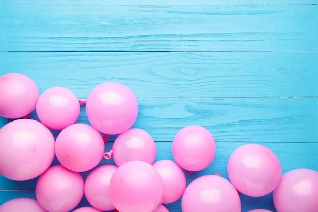 Ballons roses sur fond en bois bleu.