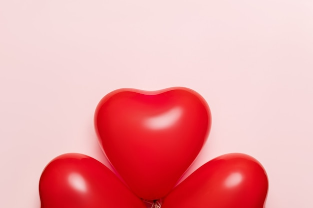 Ballons rouges en forme de coeur sur fond rose pâle. concept de la saint-valentin.