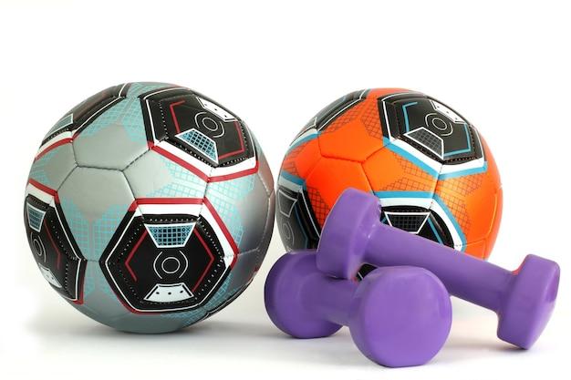 Ballons de soccer et petits haltères isolés sur blanc. équipement sportif