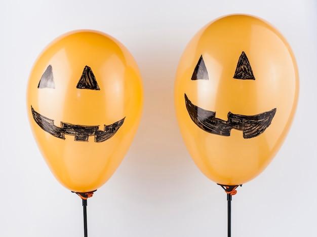 Ballons souriants décorés comme des citrouilles