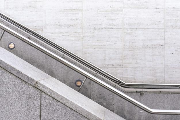 Balustrades en acier sur des escaliers en granit avec un fond de mur.