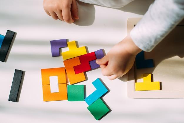Le bambin relie les pièces du puzzle coloré.