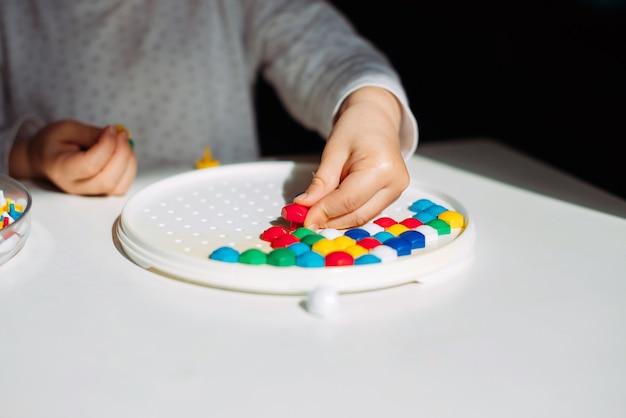 Le bambin à table joue à un puzzle.