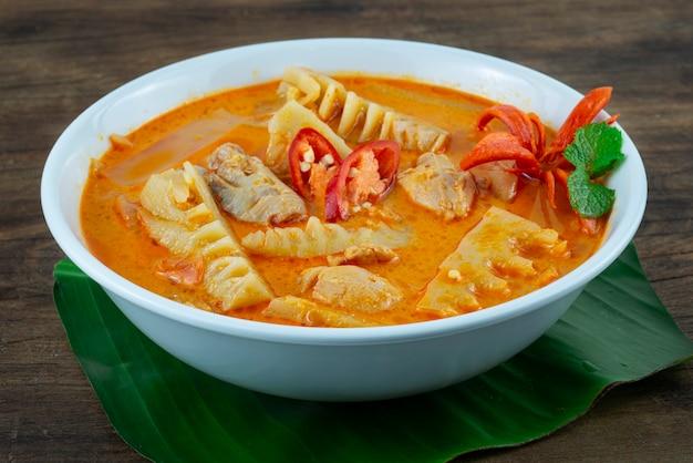 Bambou au curry rouge typique de la thaïlande avec du poulet et du lait de coco dans un bol sur fond de bois