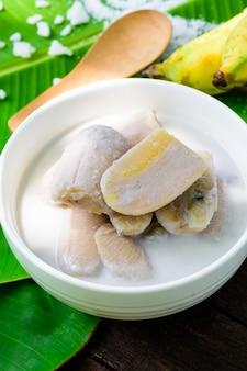 Banane au lait de coco (dessert thaï) et fond d'ingrédients.