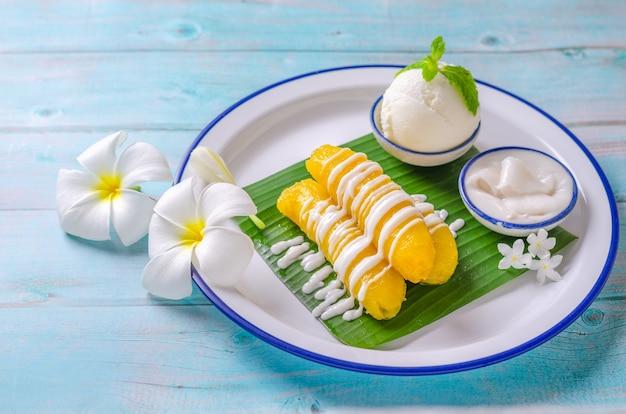 Banane au sirop garnie de lait de coco, servie avec de la crème glacée au lait de coco magnifiquement décorée dans un style thaïlandais traditionnel sur une assiette blanche.