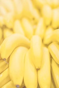Banane claire fraîche fond jaune ensoleillé texture verticale de couleur claire.