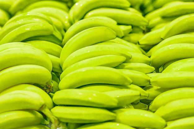 Banane claire fraîche jaune vert non mûr texture de fond