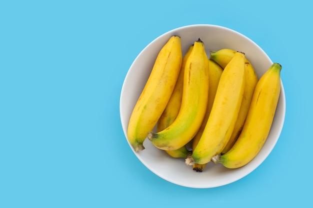 Banane dans un bol blanc sur fond bleu.