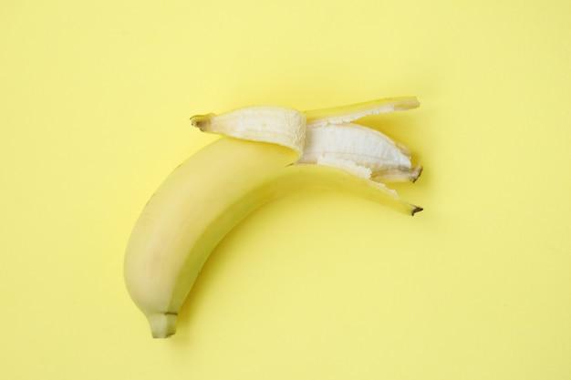 Banane fraîche sur fond jaune. modèle sans couture avec des bananes. abstrait tropical. banane sur fond jaune. banane pelée sur fond jaune