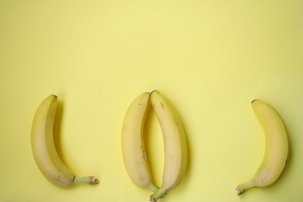Banane fraîche sur fond jaune. modèle sans couture avec des bananes. abstrait tropical. banane sur fond jaune