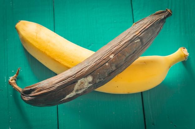 Banane fraîche et pourrie sur fond de bois