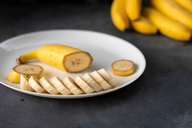 Banane fraîche en tranches dans une assiette en céramique blanche sur la table noire, préparant des ingrédients pour des petits déjeuners sains