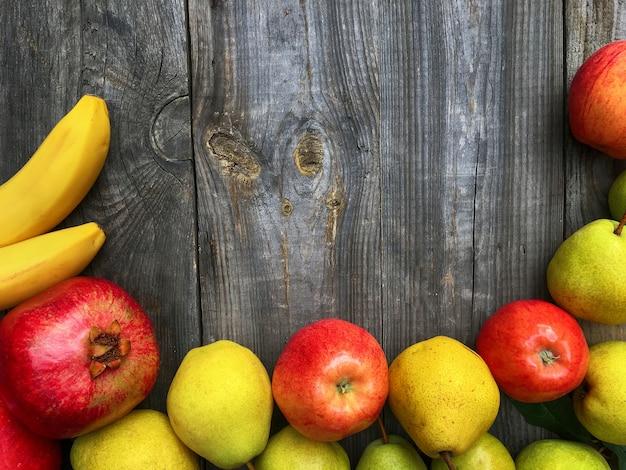 Banane, grenade, pomme, poire sur fond en bois gris