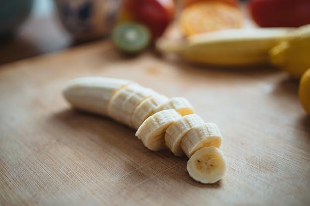 Une banane hachée sur une table en bois entourée d'autres fruits.