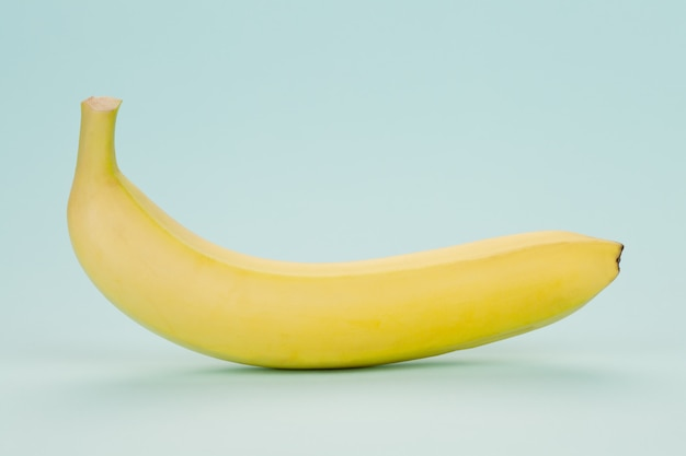 Banane jaune sur un bleu tendre. minimalisme.