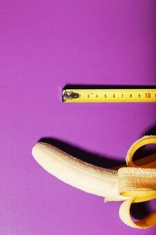 Banane jaune mesurée au ruban à mesurer sur fond rose
