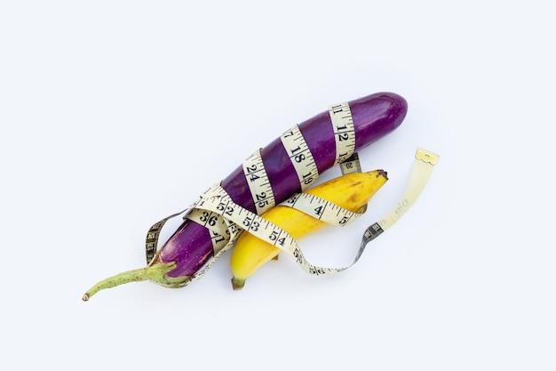 Banane avec de longues aubergines violettes enveloppées dans un ruban à mesurer sur fond blanc.