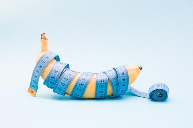 Banane mûre enveloppée dans un ruban à mesurer bleu sur une surface bleue