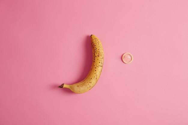 Banane mûre jaune et préservatif sur fond rose. contraception et sécurité.