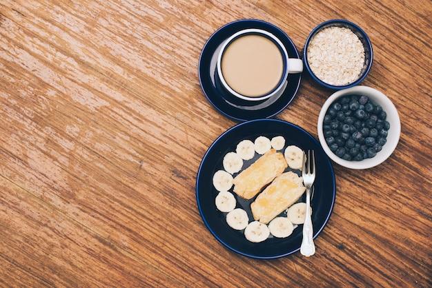 Banane; pain toasté; myrtilles; tasse de café et muesli sur fond texturé en bois