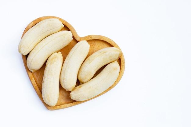 Banane pelée sur plaque en forme de coeur sur fond blanc.