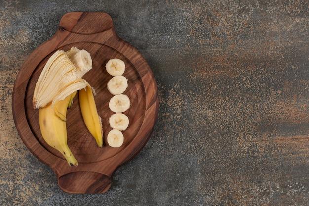 Banane pelée et tranchée sur planche de bois