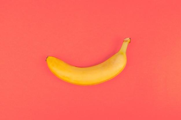 Banane en plastique jaune sur rouge