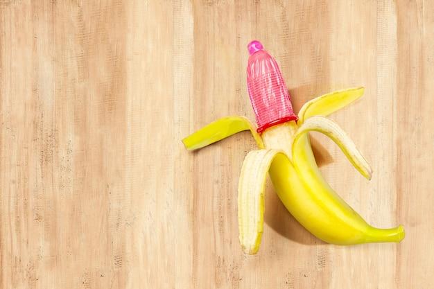 Banane avec un préservatif sur la table en bois