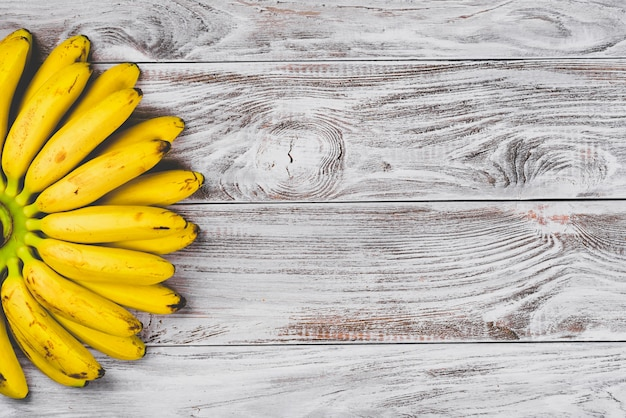 Bananes de bébé jaune biologique cru dans un tas sur fond en bois blanc vue de dessus. copyspace pour votre texte, bannière.