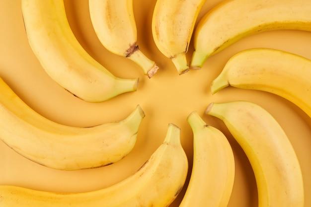 Bananes entières avec motif pelure sur fond jaune, papier peint fruits