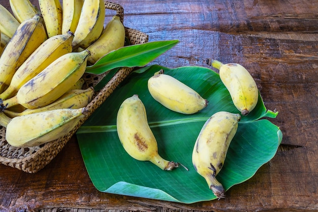 Bananes fraîches dans un panier sur une table en bois