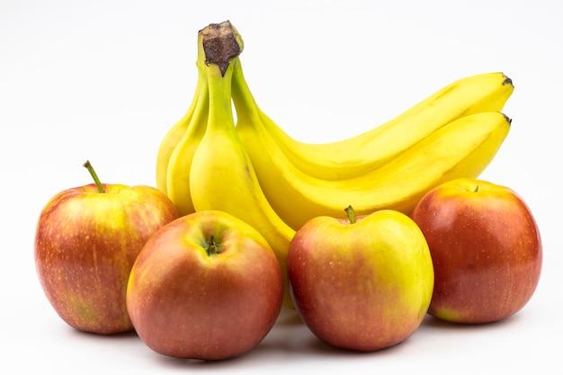 Bananes fraîches et grosses pommes rouge-jaune en gros plan isolés sur fond blanc.