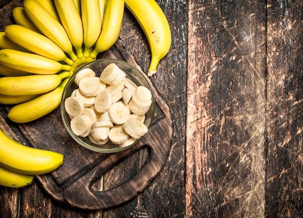 Bananes fraîches avec des morceaux hachés dans un bol. sur une table en bois.