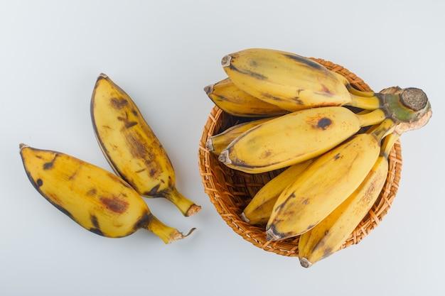 Bananes jaunes dans un panier en osier sur blanc,