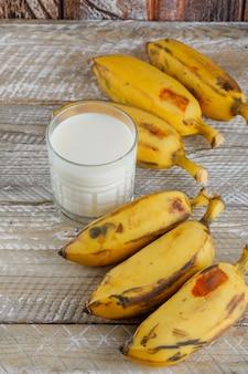 Bananes mûres avec du lait sur bois, vue grand angle.