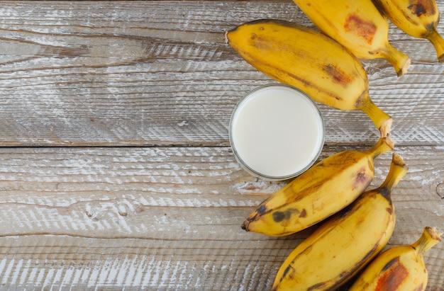 Bananes mûres avec du lait plat posé sur un bois