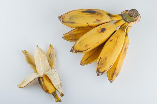 Bananes mûres jaunes sur fond blanc.