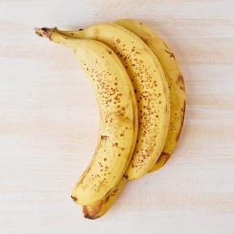 Bananes mûres avec des taches brunes sur une table en bois blanc brillant