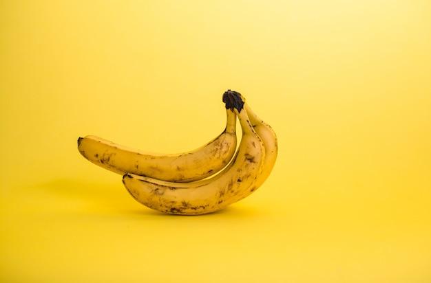 Bananes pourries sur un espace jaune avec copie espace